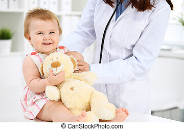 Pediatrician is taking care of baby in hospital. Little girl is being examining by doctor with stethoscope. Health care, insurance and help concept.