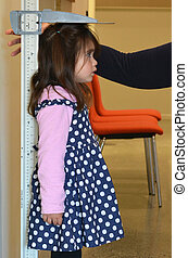 Pediatrician nurse examining child height - Pediatrician...