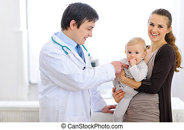 Pediatrician playing with baby on examination