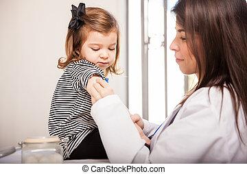 Pediatrician preparing girl for a shot