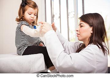 Pediatrician putting a bandage