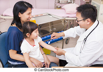 Pediatrician rubbing medication on  little girl arm wound