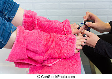 Pedicure chair spa and woman hands painting toes nail polish