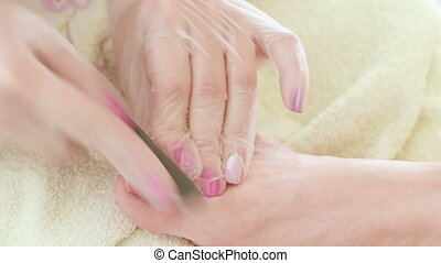 Pedicure nail technician worker perfoming procedure for foot care