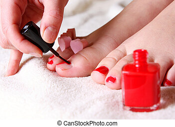 pedicure - red nail polish on her foot fingers
