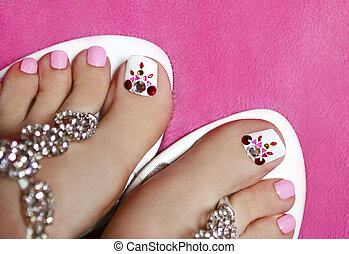 Pedicure with crystals and a different color lacquer white and pink the pink background and sandals.