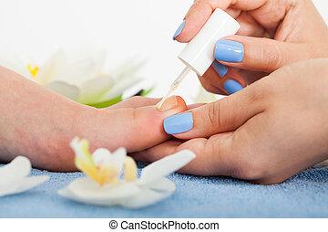 Pedicurist Applying Plain Varnish On Woman's Toenail