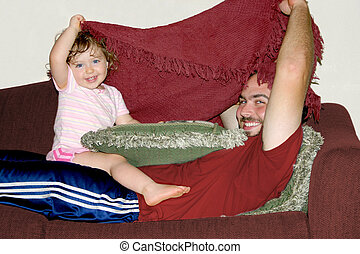a father and daughter peeking from under a blanket
