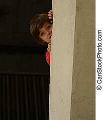 A young boy playfully plays peek a boo around a large cement pillar.