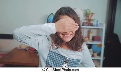 peek a boo. lifestyle little girl covered her eyes face with...