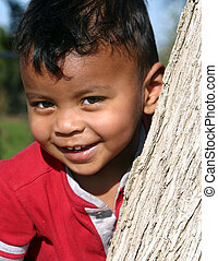 Little boy playing peek-a-boo behind a tree. Smiling face. Gorgeous interracial child.