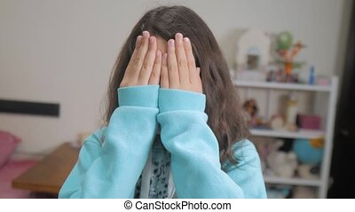 peek a boo. little girl covered her eyes face with her hands...