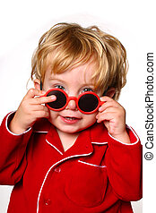 Toddler peeking over a pair of red sunglasses