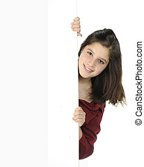 A pretty preteen peeking around a white wall and on a white background.