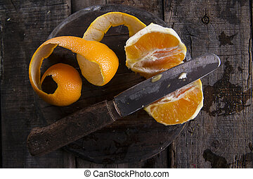 Peel an orange with the use of an old knife on the table