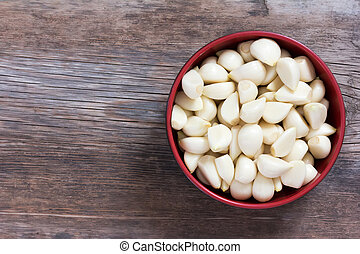 peeled cloves of garlic on an old wooden background closeup top view with space for text