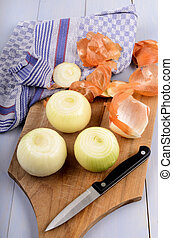 peeled large white onions with kitchen knife on a wooden board