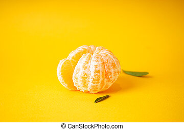 Peeled mandarin with green leaves on a yellow background.
