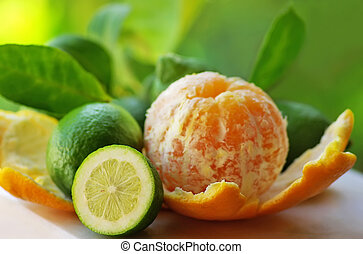 Peeled orange, and green lemons