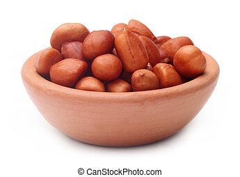 Peeled peanuts on a clay pot