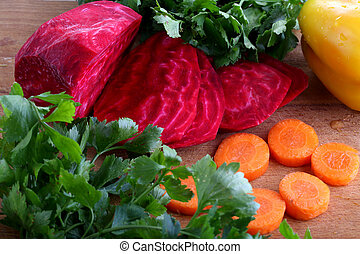 peeled red beets and fresh carrots for salad on a wooden table