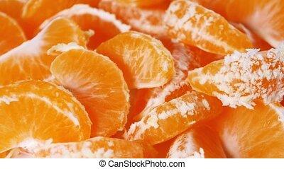 Peeled rotating mandarin segment, close up, as background...
