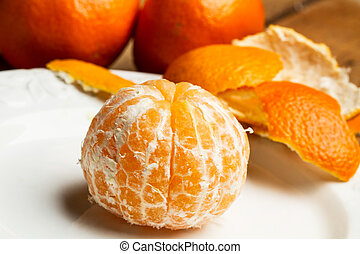 Peeled tangerine on a white plate
