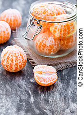 peeled  tangerine or mandarin fruit in glass jar on wooden table