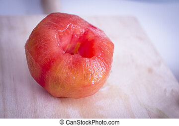 Peeled tomato on wooden cutting board