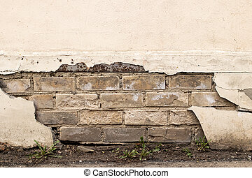 Peeling paint on an old brick wall