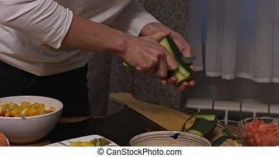 Peeling vegetable - cucumber - Female woman hands peeling...