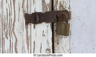 Peeling Wooden Door Secured By Padlock Hasp And Staple