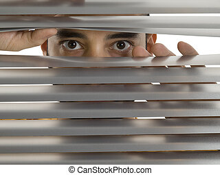 Peeping Tom - A man looks to the camera through the blinds.