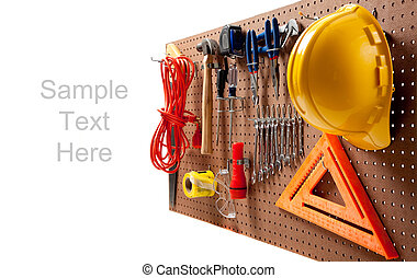 Peg board with hardhat, extension cord, flashlight, hammer, screw driver, caution tape, carpenter's square and pliers