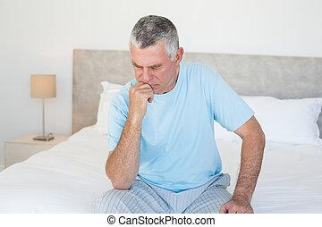 peinzend, hogere mens, zitting op het bed