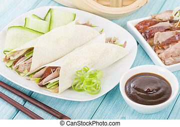 Peking Duck - Chinese roast crispy duck, cucumber and spring onions wrapped in pancakes served with hoisin sauce.