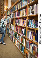 pelirrojo, estudiante, toma, libro, de, estante libros, en, el, biblioteca