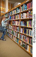 pelirrojo, estudiante, toma, un, libro, de, estante libros, en, el, biblioteca