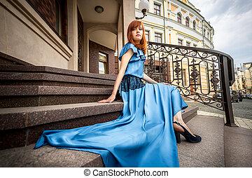 pelirrojo, mujer, en, vestido azul, posar, en, escaleras, en, edificio viejo