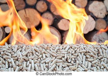 Pellets- Biomas - Pine pellets in flames- behind flames ara ...