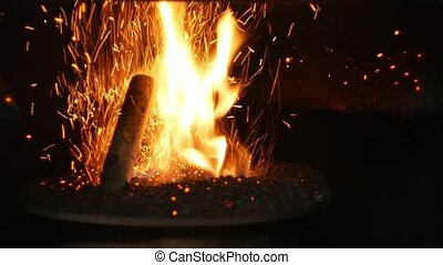 Pellets fire burn with spruce sawdust into the delivery strew bio wooden pallets to industrial modern boiler, sparks fly out and flames fire detail , biofuels made from compressed biomass fuel