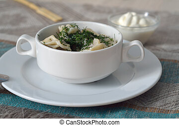 Pelmeni in a bowl with sour cream