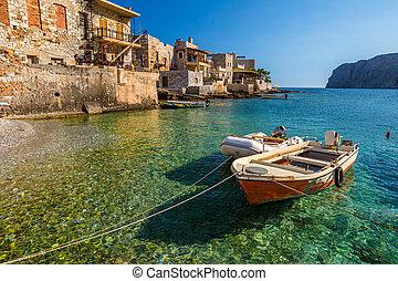 Fishing boats in the clear tropical waters of Gerolimenas, Mani Peninsula, Lakonia, Peloponnese, Greece.