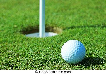 pelota de golf, en, hierba verde, delante de, agujero