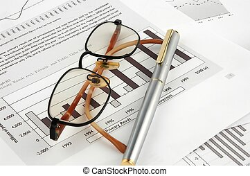 Pen and glasses on financial charts