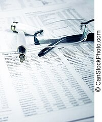 pen and glasses on financial chart