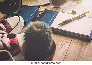 Pen and notebook with personal accessory on wooden table. Travel concept.