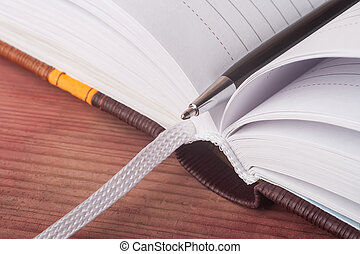 pen and open daily log on wooden table