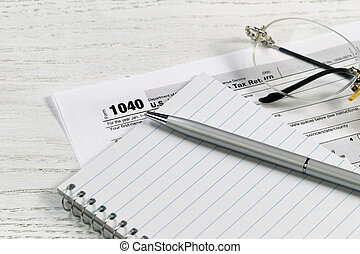 Pen and paper with tax forms on white desktop