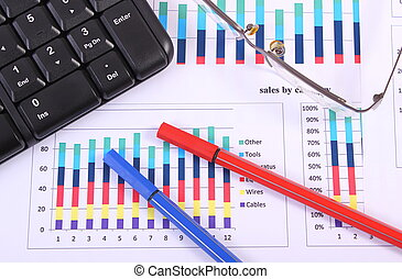 Pen, glasses and computer keyboard on financial graph, business concept